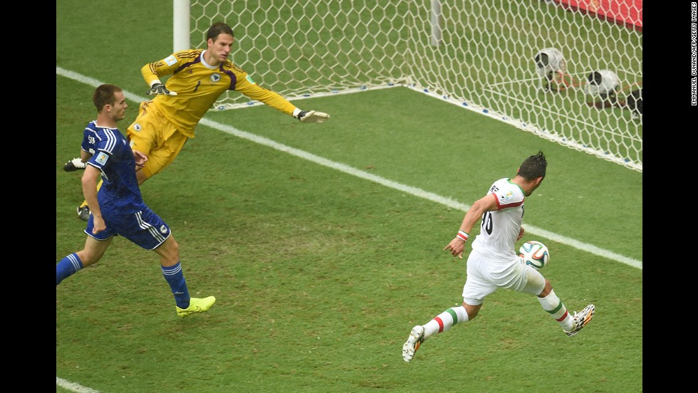 Iran forward Reza Ghoochannejhad, right, kicks to score his team's first goal past Bosnia-Herzegovina goalkeeper Asmir Begovic as Bosnia-Herzegovina defender Toni Sunjic runs during the match.