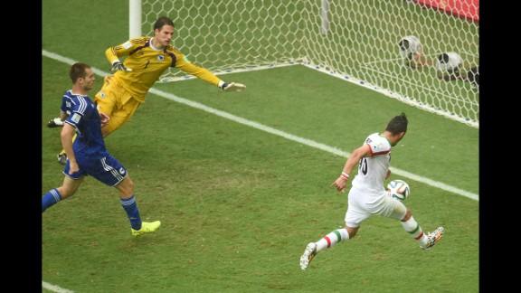 Iran forward Reza Ghoochannejhad, right, kicks to score his team's first goal past Bosnia-Herzegovina goalkeeper Asmir Begovic as Bosnia-Herzegovina defender Toni Sunjic runs during the match.