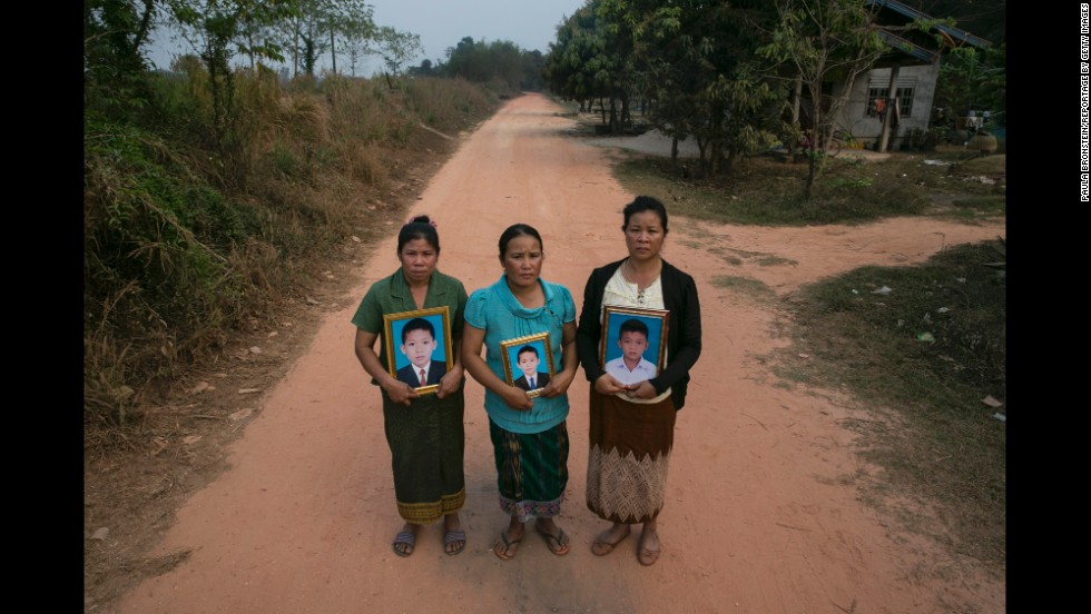 Three mothers hold framed portraits of their sons on the same dirt road in Laos where they were killed in January. The children found a cluster bomb and started playing with it like it was a toy.