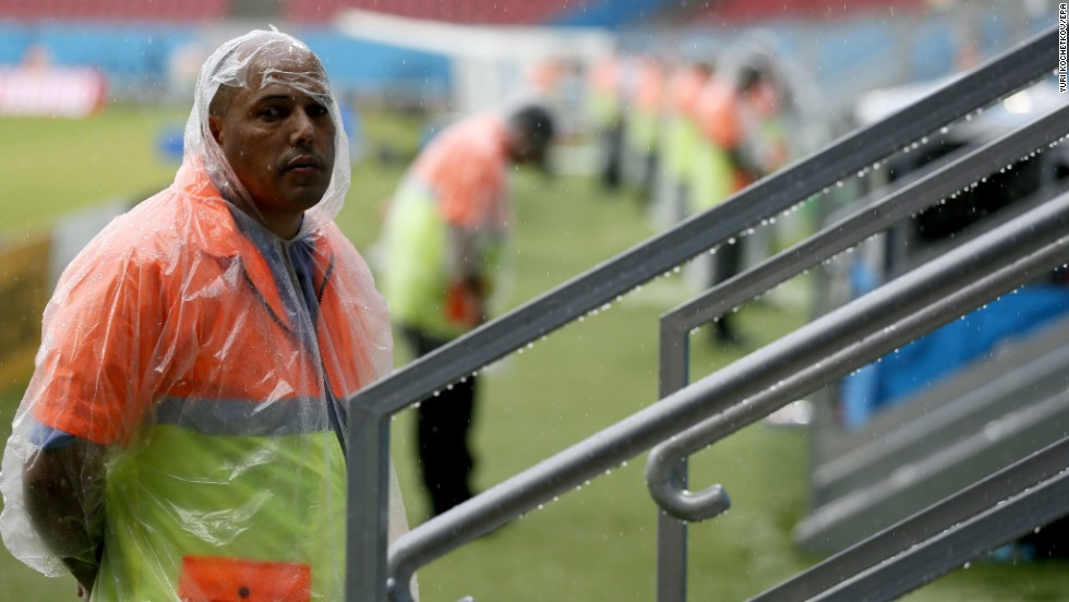 A steward braves the elements prior to the match.