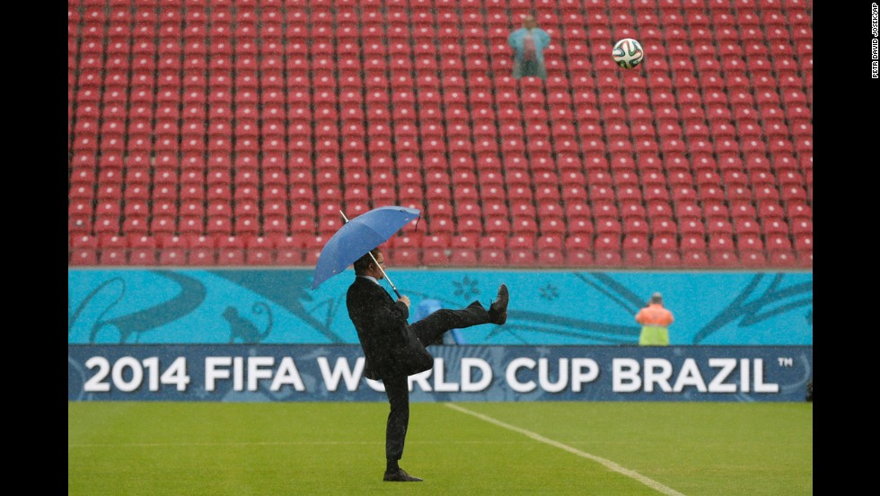 A FIFA official tests the pitch as rain pours down prior to the match.