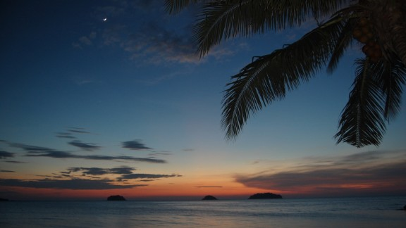 The sun sets over the Andaman Sea off the coast of Phuket, Thailand, in July 2013, as seen in this photo by John Vogel.