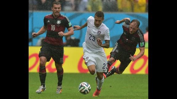 Lukas Podolski and Benedikt Hoewedes of Germany chase after Fabian Johnson of the United States.