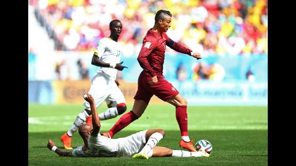 Andre Ayew of Ghana tackles Cristiano Ronaldo of Portugal.