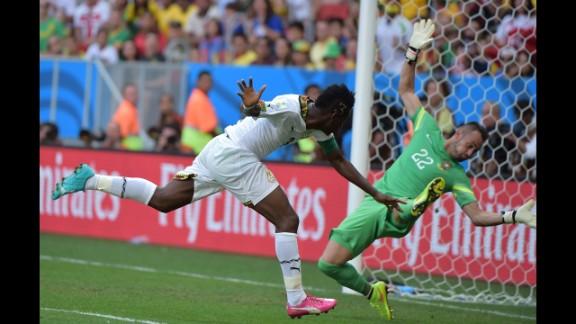 Ghana forward and captain Asamoah Gyan, left, scores past Portugal