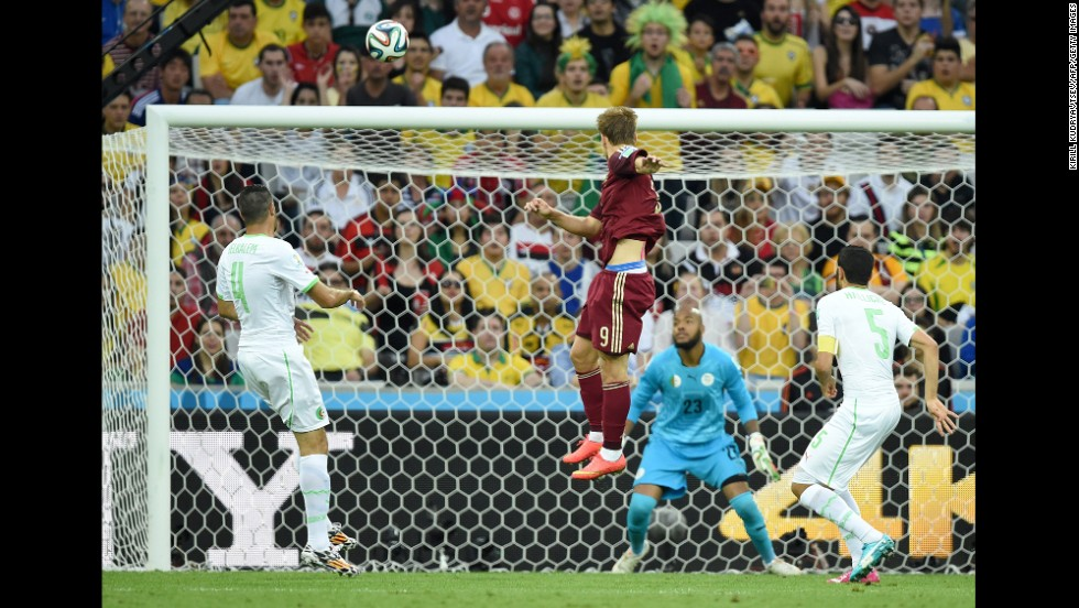 Russia forward Alexander Kokorin, center, scores his team's first goal past Algeria's goalkeeper Rais Mbohli, in blue.