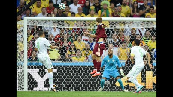 Russia forward Alexander Kokorin, center, scores his team's first goal past Algeria's goalkeeper Rais Mbohli, in blue.