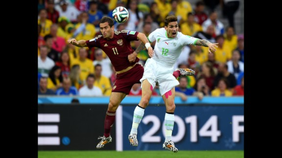 Aleksandr Kerzhakov of Russia and Carl Medjani of Algeria compete for the ball.