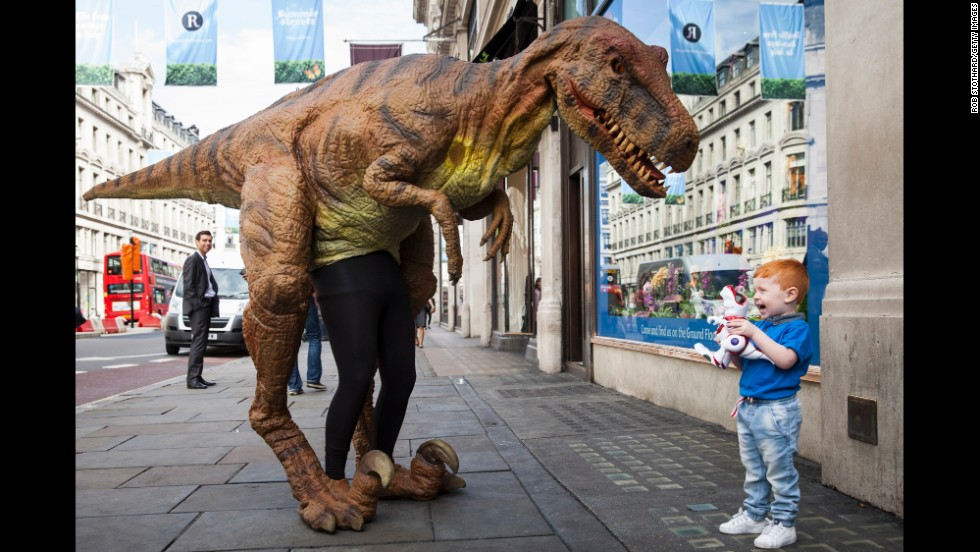 Tristan Robertson-Jeyes, 3, reacts to a person in a dinosaur costume outside Hamleys toy shop in London on Thursday, June 26.