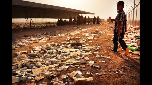 A child walks over discarded water bottles and trash at a registration area at the displacement camp in Khazair on June 26.
