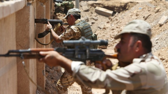 Kurdish Peshmerga fighters take their positions behind a wall on the front line of the conflict with ISIS militants in Tuz Khormato, Iraq, on Wednesday, June 25.