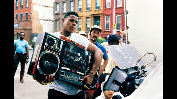 """The film is set on a hot day in Brooklyn, New York, and follows the lives of several characters. One of them, Radio Raheem (Bill Nunn), likes to walk around the neighborhood playing Public Enemy's """"Fight the Power"""" at high volume, annoying some and entertaining others."""