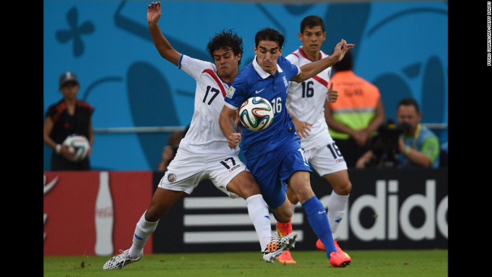 Yeltsin Tejeda, left, and Cristian Gamboa, right, of Costa Rica defend against Lazaros Christodoulopoulos of Greece.