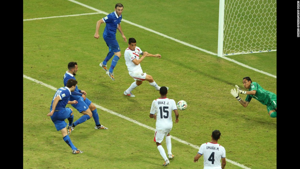 Sokratis Papastathopoulos of Greece, left, shoots and scores late in the second half to tie Costa Rica during a game in Recife, Brazil, on Sunday, June 29. The elimination-round game ended with a final score of 1-1. Costa Rica advanced by winning a penalty kick shootout.