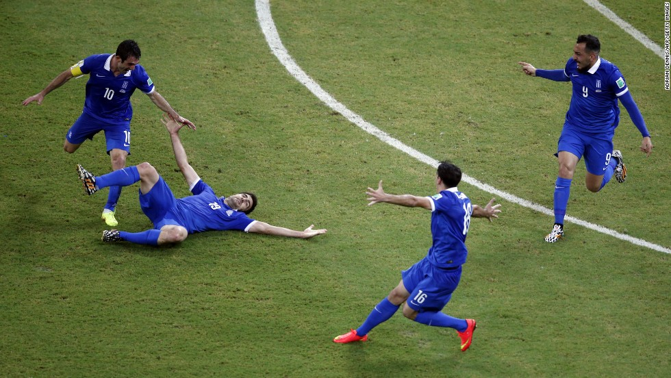 Greece's Sokratis Papastathopoulos, on the ground, celebrates with teammates after scoring his team's equalizing goal against Costa Rica.