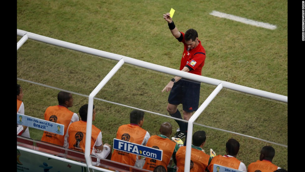 Referee Benjamin Williams gives a yellow card to Costa Rica's Oscar Esteban Granados on the sideline.