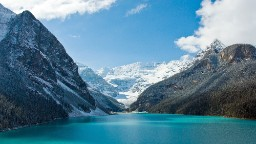 An alpine lake with sparkling blue waters, Alberta's Lake Louise in Banff National Park sits at the base of a cluster of glacier-clad peaks. The lake offers paddling in summer and an outdoor skating rink in winter.