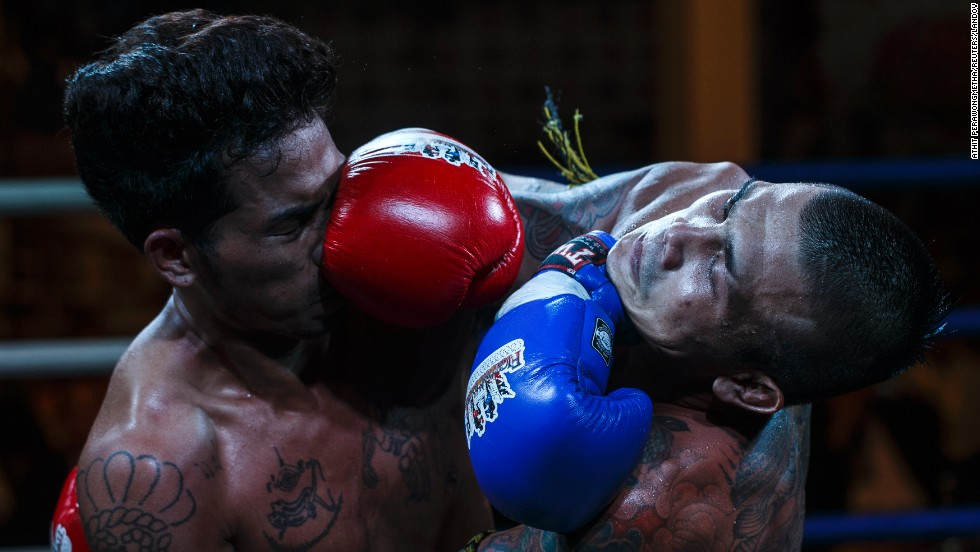 "Thai prisoner Chanmansuk P.U. Suphap, right, fights Mnajande Msidmata of Myanmar during a Muay Thai bout Thursday, June 26, at the Klong Prem prison in Bangkok, Thailand. A Muay Thai program <a href=""http://cnnphotos.blogs.cnn.com/2014/06/01/thailands-science-of-8-limbs/"">began at the prison last year</a> to help rehabilitate inmates. For some, success against foreign challengers has knocked time off their sentences."