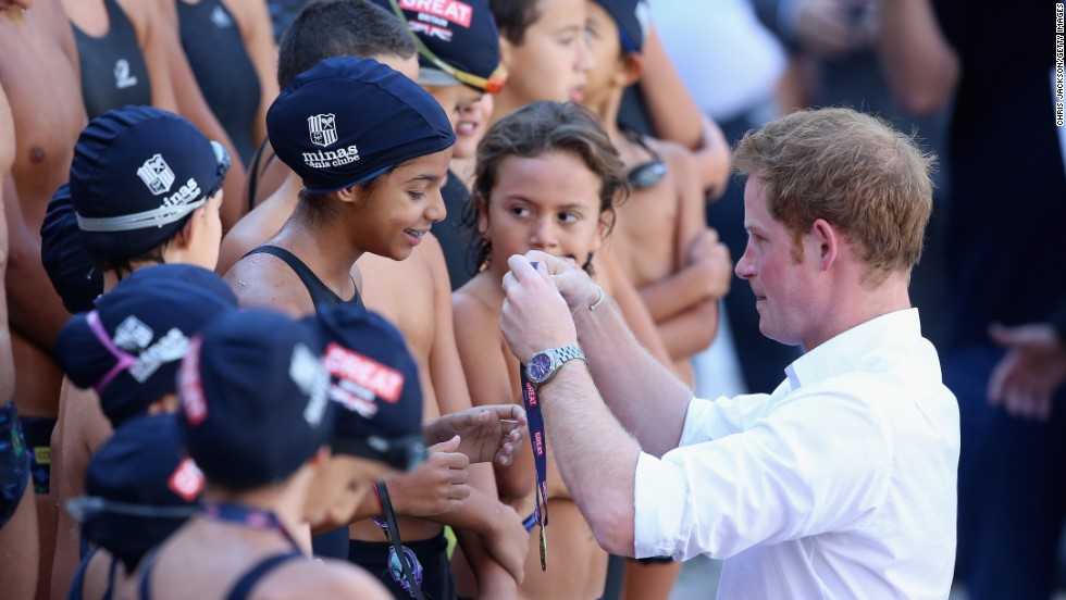 Britain's Prince Harry presents medals to young swimmers during a visit to a sports club in Belo Horizonte, Brazil, on Tuesday, June 24. He was on a four-day tour of Brazil that was followed by two days in Chile.