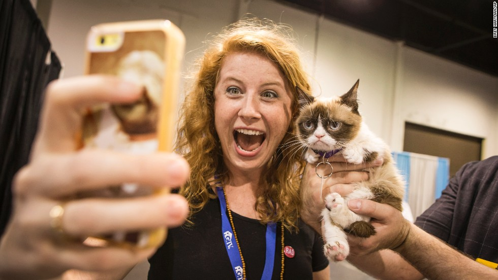 "A fan takes a selfie with <a href=""http://money.cnn.com/2013/09/18/news/companies/grumpy-cat-friskies/"">""Grumpy Cat,""</a> the Internet celebrity famous for her perpetual scowl, on Friday, June 27, at the Anaheim Convention Center in Anaheim, California. The cat, whose real name is Tardar Sauce, is the official ""spokescat"" for Friskies cat food and <a href=""http://www.thefriskies.com"" target=""_blank"">its award show</a> for the best original cat videos."