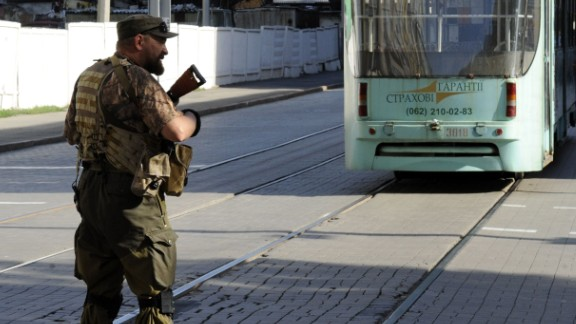 A pro-Russian militant stops the tram traffic as he takes part in the storm of the regional police station in the centre of the eastern Ukrainian city of Donetsk on July 1, 2014. Ukrainian tanks and fighter bombers on July 1 launched a ferocious assault against pro-Russian separatist insurgents after rejecting European attempts to save a tenuous 10-day truce. AFP PHOTO/ ALEXANDER KHUDOTEPLYAlexander KHUDOTEPLY/AFP/Getty Images