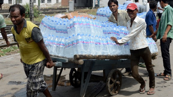 Workers in New Delhi pull a cart carrying water bottles on June 27.