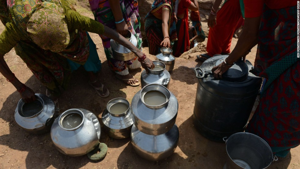 Villagers in Surendranagar, India, use pots to collect drinking water from a man-made well on June 1.
