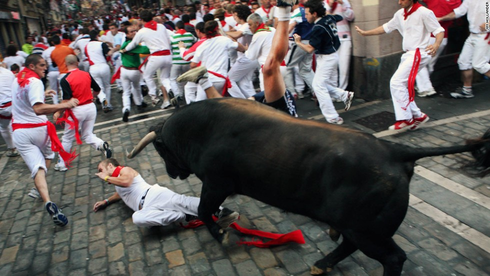 "One runner tries to protect himself from a fighting bull from the Fuente Ymbro ranch as another is upside-down with both feet in the air during the third ""encierro,"" or Running of the Bulls in Pamplona's Fiesta de San Fermin on July 9, 2008."