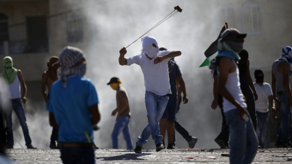 A masked Palestinian protester uses a slingshot to throw stones towards Israeli police (unseen) during clashes in the Shuafat neighborhood in Israeli-annexed Arab East Jerusalem, on July 3, 2014.