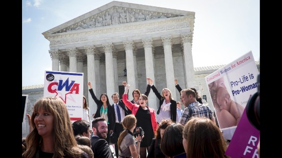 The legal team representing craft-store chain Hobby Lobby Stores Inc. celebrates on the steps of the U.S. Supreme Court after a ruling is announced in Washington, D.C., U.S., on Monday, June 30, 2014. The Supreme Court dealt a blow to President Barack Obama's health-care law, ruling that closely held companies can claim a religious exemption from the requirement that they offer birth-control coverage in their worker health plans.