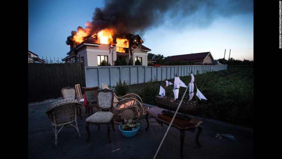"A house in the Ukrainian village of Nikolayevka catches fire Tuesday, July 1, after a mortar attack in the suburbs of Luhansk. Ukrainian forces <a href=""http://www.cnn.com/2014/05/27/world/gallery/ukraine-after-election/index.html"">continue to clash</a> with pro-Russia separatists in the eastern part of the country."