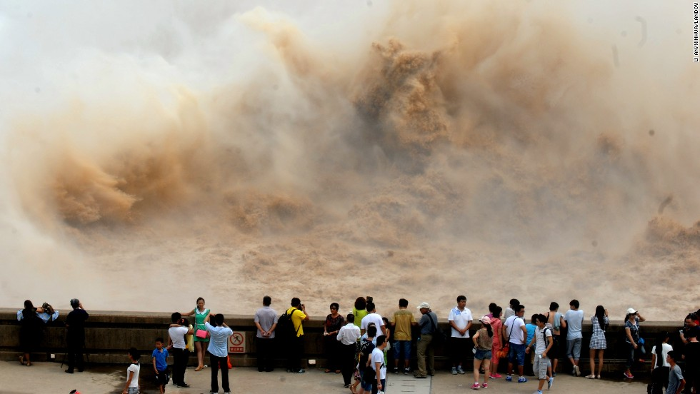 Tourists in Jiyuan, China, look at water cascades generated by the Xiaolangdi Dam on Monday, June 30.