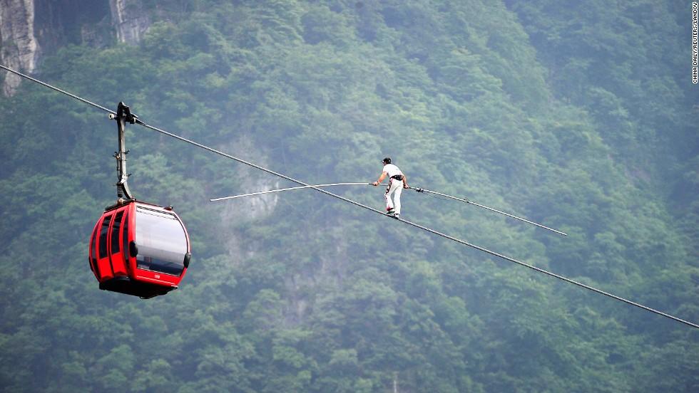Swiss acrobat Freddy Nock balances on a cableway over a mountain Saturday, June 28, at Tianmen Mountain National Park in Zhangjiajie, China. Nock attempted to walk the entire 743-meter (2,438-foot) cableway, but according to local media he gave up about halfway through because of the mountain's steep inclination.