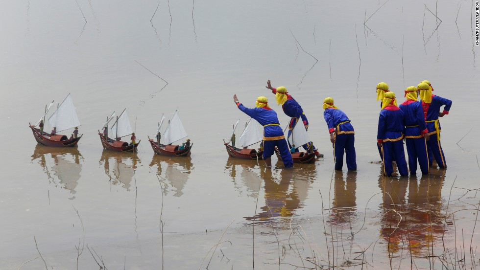 "Fishermen from Vietnam's Ly Son island release miniature fishing boat models with artificial soldiers during a re-enactment of the Khao Le The Linh ceremony Sunday, June 29, at a cultural village in Dong Mo, Vietnam. The Khao Le The Linh ceremony, observed annually in March by fishermen in Ly Son, <a href=""http://en.vietnamplus.vn/Home/Ceremony-honouring-Hoang-Sa-sailors-gets-heritage-title/20134/33778.vnplus"" target=""_blank"">pays homage to men</a> who were assigned to protect the Hoang Sa and Truong Sa archipelagos many years ago."