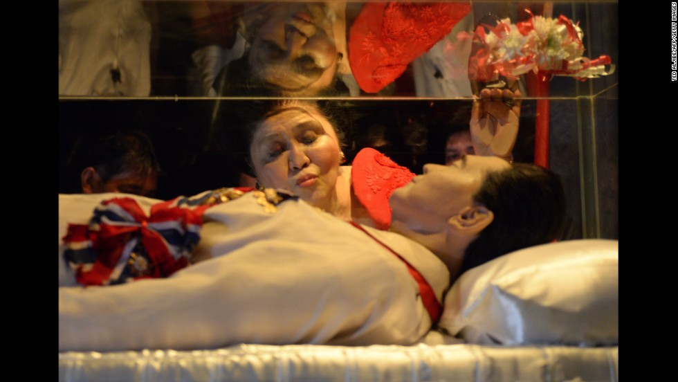 Former Philippines first lady Imelda Marcos kisses the glass coffin of her late husband, former president Ferdinand Marcos, on her 85th birthday Wednesday, July 2, in Batac, Philippines. Ferdinand Marcos has been dead since 1989.