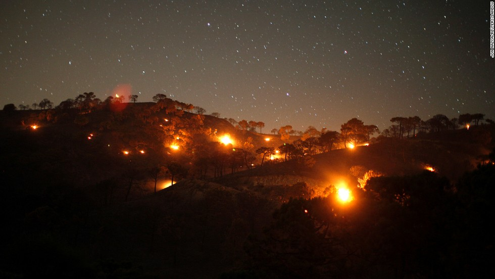 Small forest fires burn on a mountain near Competa, Spain, on Monday, June 30. A wildfire forced 600 people to evacuate their homes, according to local media.
