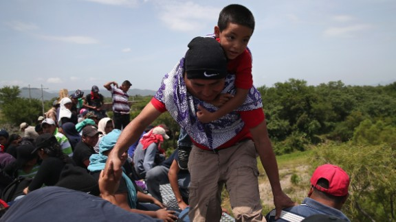 Caption:IXTEPEC, MEXICO - AUGUST 06: Central American immigrants arrive on top of a freight train for a stop on August 6, 2013 in Ixtepec, Mexico. Thousands of Central American migrants ride the trains, known as