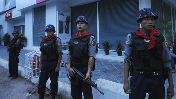Myanmar police guard on a street in Mandalay, after imposing an overnight curfew in the country's second largest city. The curfew was introduced after two nights of religious violence between Buddhists and Muslims that left two people dead.