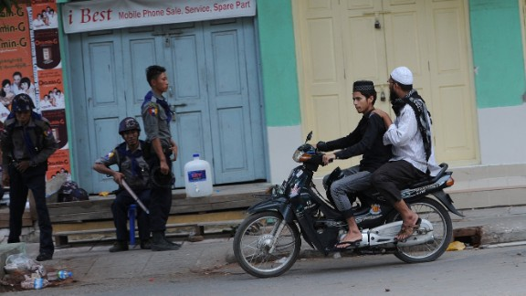 Two Muslims ride past officers imposing order in the streets of Mandalay, Myanmar's multicultural, multi-faith second city. Muslims, who comprise about 5% of Myanmar's population, have been the target of occasional mob violence at the hands of the country's Buddhist majority in recent years,