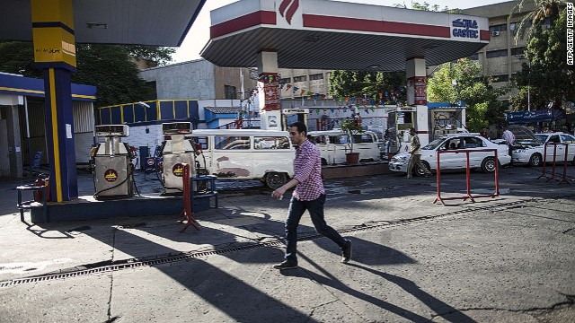 Egyptians gather at a petrol station on July 5, 2014 in Cairo as the government drastically raised fuel prices to tackle a bloated subsidy system. The government raised the price of 92 octane gasoline, which sold at 1.85 pounds ($0.36) a litre, to 2.6 pounds, and 80 octane gas from 0.9 pounds to 1.6 pounds a litre, in a potentially unpopular move that might blow back on newly elected President Abdel Fattah al-Sisi. AFP PHOTO / MAHMOUD KHALEDMAHMOUD KHALED/AFP/Getty Images
