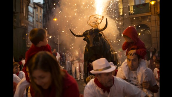 "Revelers run away followed by a flaming fake bull ""Toro de fuego"" during the second  day of the 2014 San Fermin fiestas in Pamplona, Spain, Monday, July 7, 2014. Revelers from around the world arrive to Pamplona every year to take part on some of the eight days of the running of the bulls glorified by Ernest Hemingway"