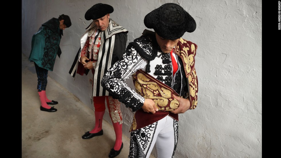 Bullfighter Miguel Abellan adjusts his capote before the ritual entrance to the arena on July 7.
