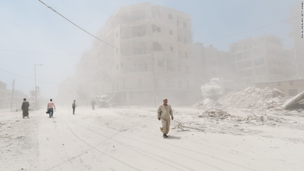 People walk on a dust-filled street after a reported barrel-bomb attack in Aleppo on Monday, July 7.