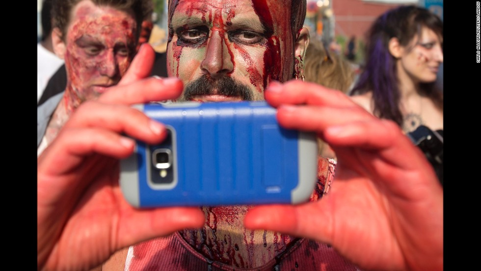 "A participant of the ""Zombie Takeover of Coney Island"" takes a selfie as he walks in the Brooklyn, New York, neighborhood on Wednesday, July 2."