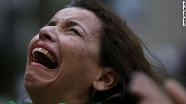 A Brazilian soccer fan cries as she watches a live telecast of the semifinals World Cup soccer match between Brazil and Germany in Belo Horizonte, Brazil, Tuesday, July 08, 2014. (AP Photo/Bruno Magalhaes)