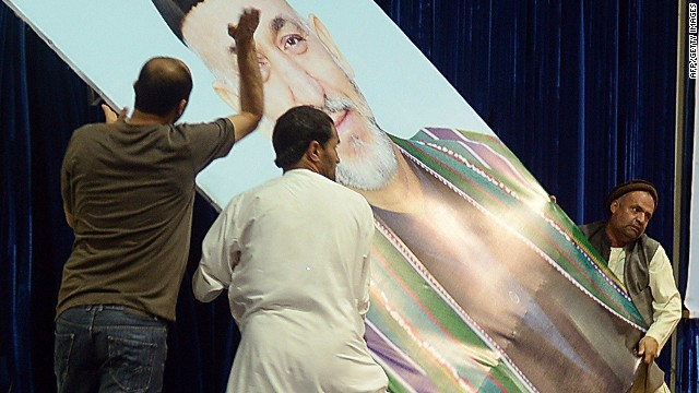 "Afghan supporters of presidential candidate Abdullah Abdullah beat a poster bearing the image of President Hamid Karzai which was ripped down from the stage at a rally in Kabul on July 8, 2014. Presidential candidate Abdullah Abdullah claimed victory in Afghanistan's disputed election, blaming fraud for putting him behind in preliminary results as fears rise of instability and ethnic unrest. Abdullah told a rally of thousands of rowdy supporters in Kabul that he would fight on to win the presidency, but he called for patience from loyalists who demanded he declare a ""parallel government"" to rule the country. AFP PHOTO/SHAH MaraiSHAH MARAI/AFP/Getty Images"