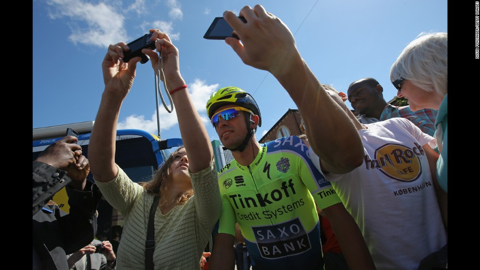 Cyclist Alberto Contador pauses for a photo with fans in Leeds, England, before the start of the Tour de France on Saturday, July 5.
