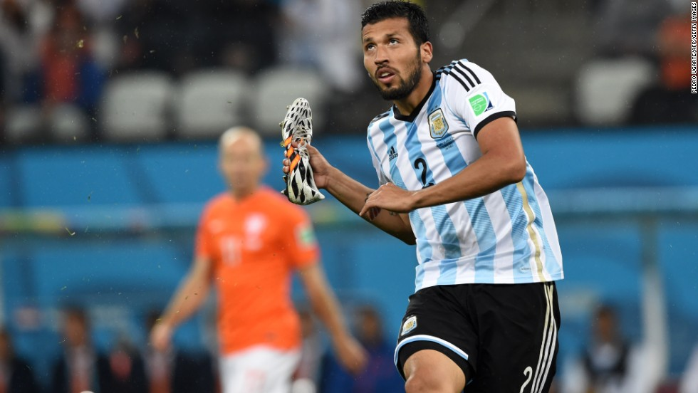 Caption:Argentina's defender Ezequiel Garay holds a boot during the semi-final football match between Netherlands and Argentina of the FIFA World Cup at The Corinthians Arena in Sao Paulo on July 9, 2014. AFP PHOTO / PEDRO UGARTE (Photo credit should read PEDRO UGARTE/AFP/Getty Images)