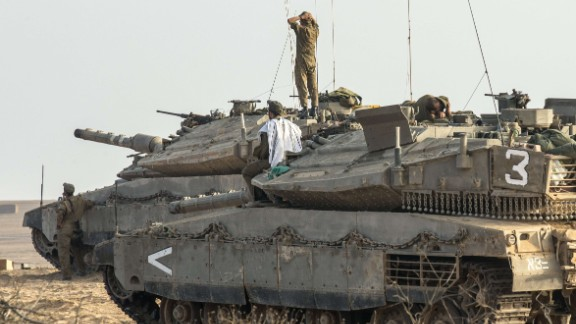 Israeli soldiers stand on Merkava tanks in an army deployment area near Israel's border with Gaza on July 9, 2014.