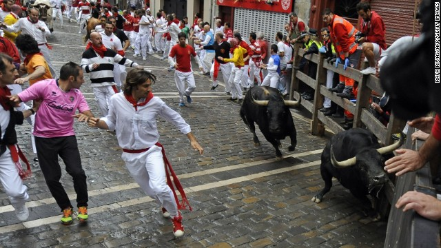 Participants run in front of Victoriano del Rio Cortes' bulls during the third bull-run of the San Fermin Festival in Pamplona, northern Spain, on July 9, 2014. The festival is a symbol of Spanish culture that attracts thousands of tourists to watch the bull runs despite heavy condemnation from animal rights groups. AFP PHOTO / RAFA RIVAS        (Photo credit should read RAFA RIVAS/AFP/Getty Images)